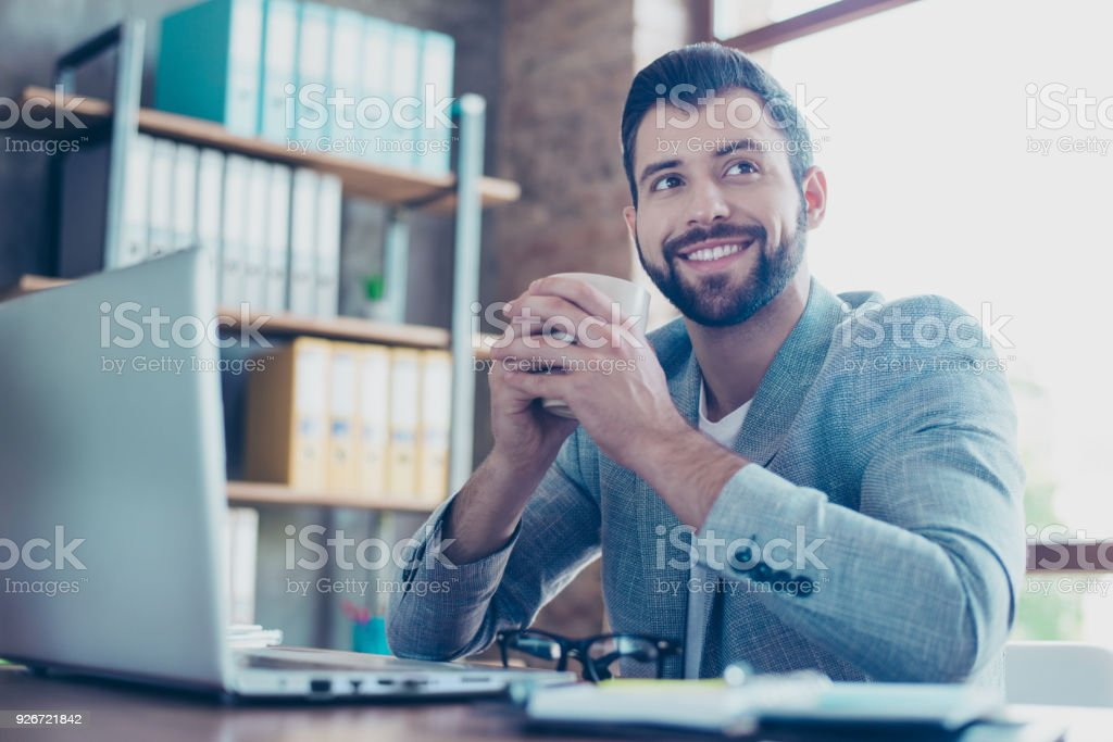 Portrait of handsome, brunet, smiling, happy lawyer, holding mug of tea in his hand, looking to the side, sitting in workstation stock photo