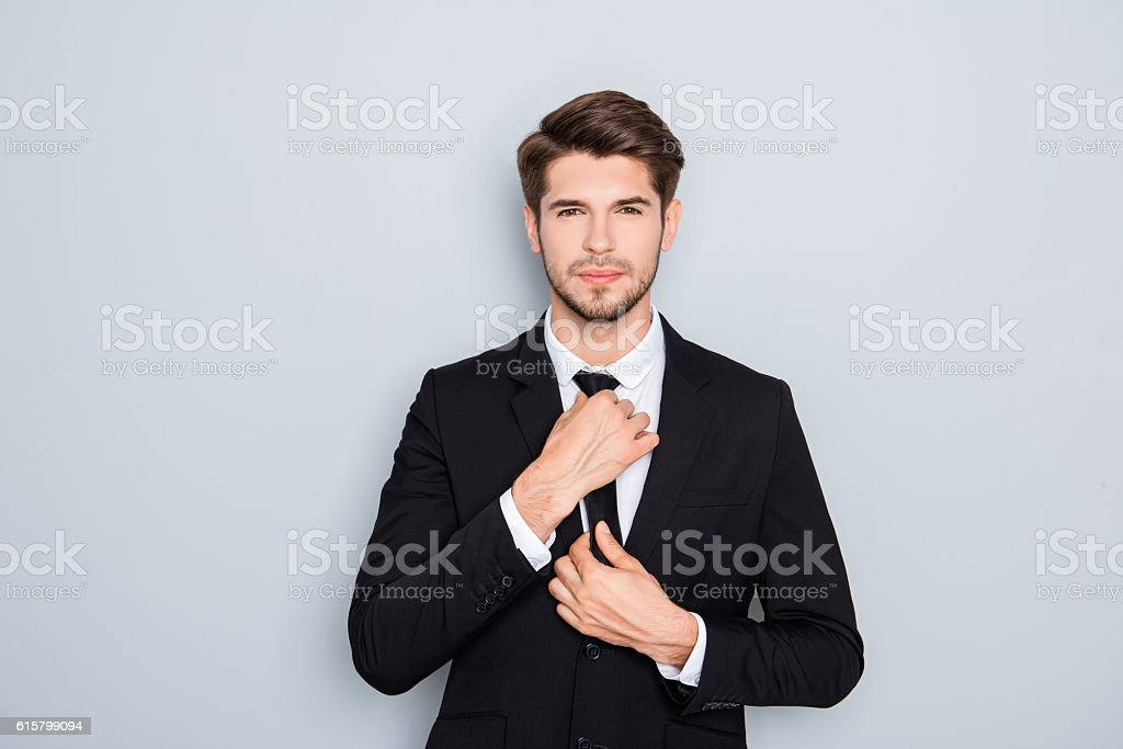 Portrait of handsome businessman correcting tie on gray background stock photo