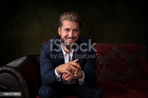 istock Portrait of handsome businessman in elegant suit sitting on couch and holding a cigar 1094370852