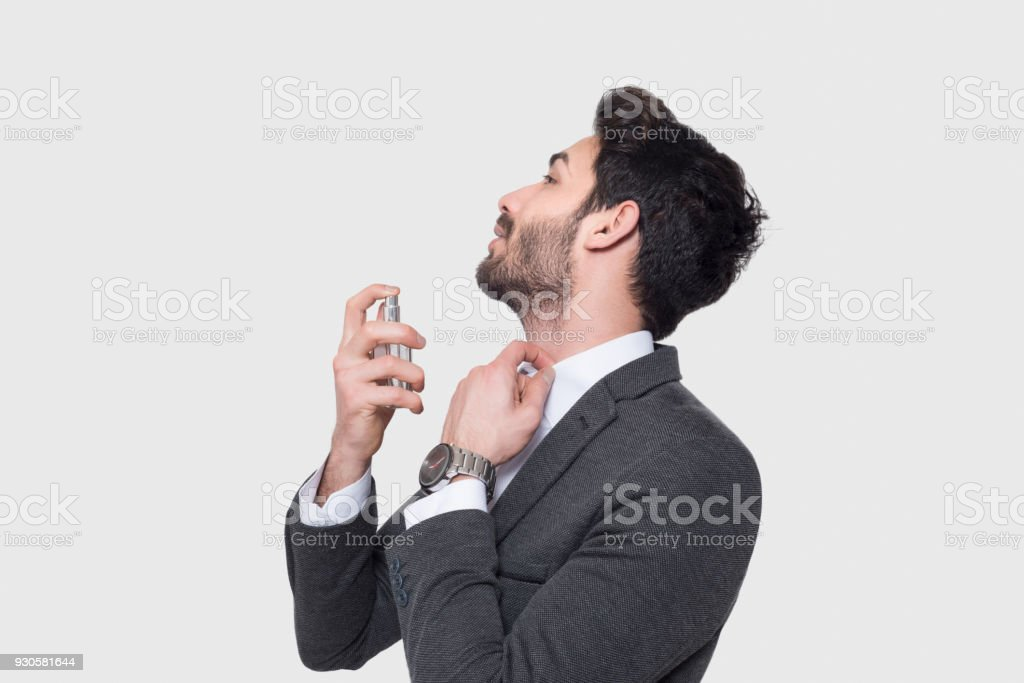 Portrait of handsome businessman in suit applying perfume over gray background stock photo