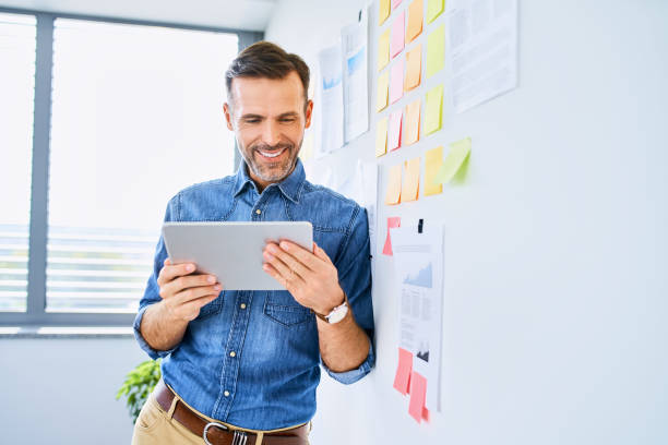 Portrait of handsome businessman leaning against office wall and looking at tablet stock photo