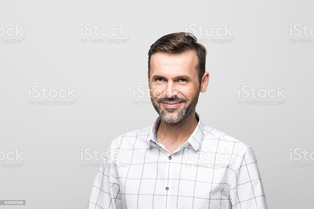 Portrait of handsome businessman smiling at camera, grey background Portrait of handsome successful businessman wearing white shirt, smiling at the camera. Studio portrait, grey background. 30-39 Years Stock Photo