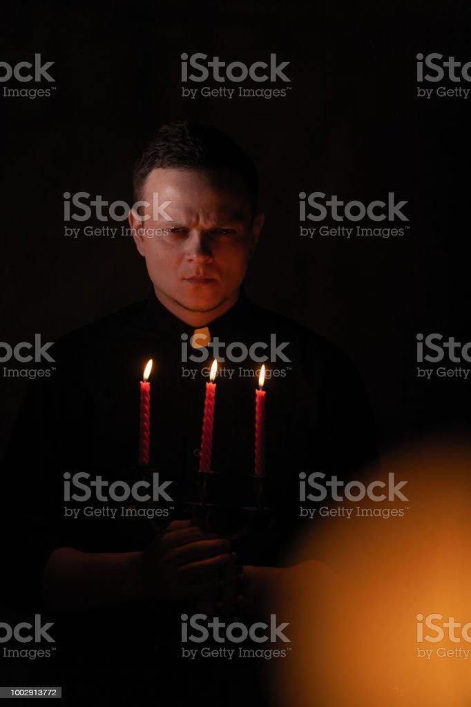 Portrait of handsome catholic priest or pastor with dog collar, dark red background. with three red candle in the hand stock photo