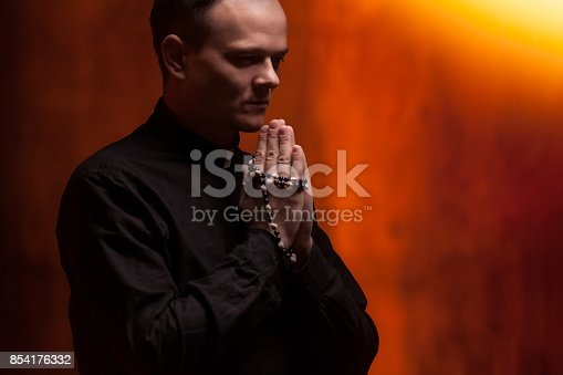 istock Portrait of handsome catholic priest or pastor with dog collar, dark red background. 854176332