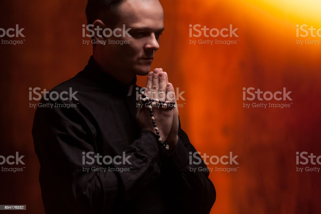 Portrait of handsome catholic priest or pastor with dog collar, dark red background. stock photo