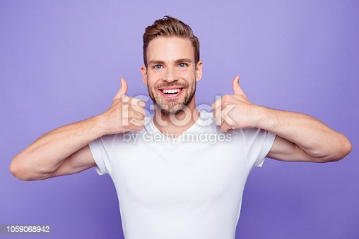 1092211952 istock photo Portrait of handsome cheerful attractive bearded content guy in white tshirt with stubble, bristle, showing two thumbs-up, isolated over bright vivid violet purple background 1059068942