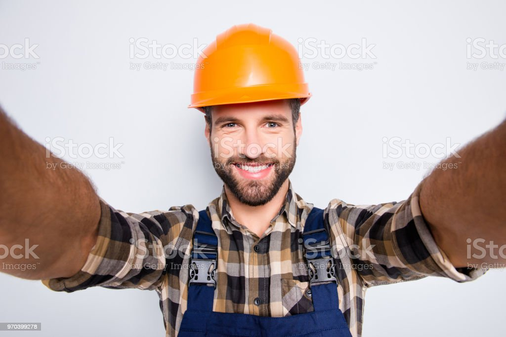 0a0743fe17c Portrait of handsome cheerful repairer in safety helmet with stubble  shooting selfie on smart phone with
