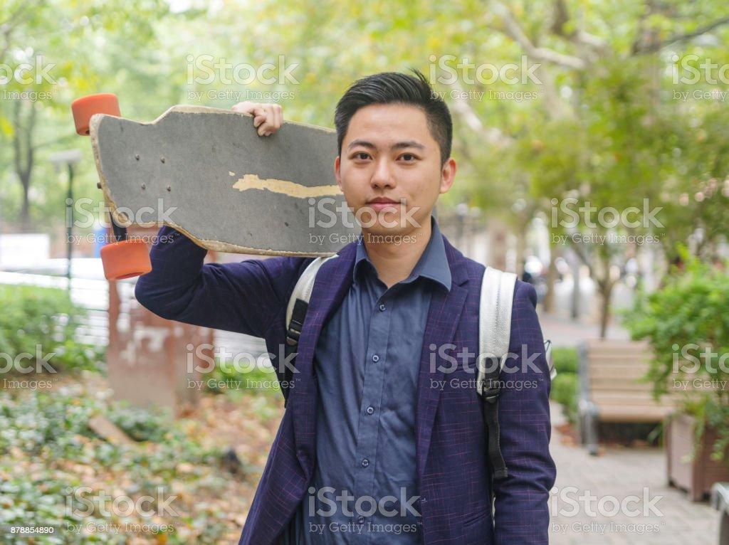 Porträt von hübschen Mann junge Chinesen halten seinen Skate Board auf seiner Schulter und lächelt in die Kamera. – Foto