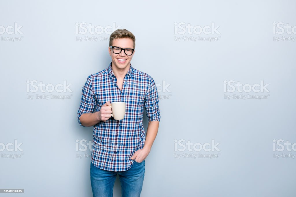 Portrait of handsome confident attractive with toothy smile intelligent it-specialist holding cup of fresh green tea keeping hand in pocket of denim trousers isolated on gray background copy-space royalty-free stock photo