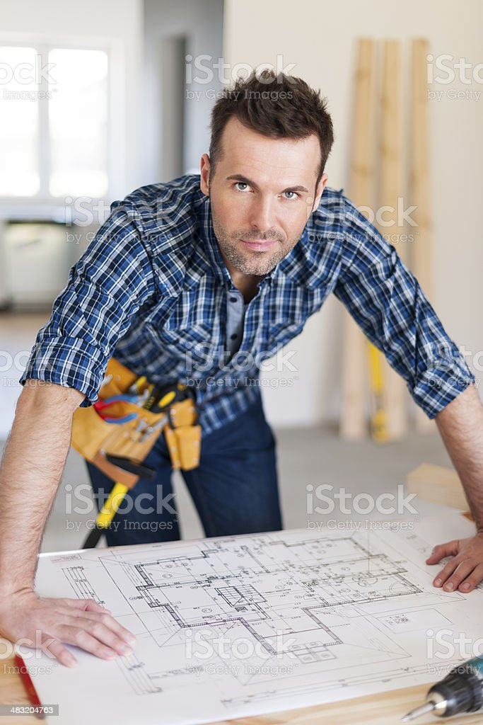 Portrait of handsome construction worker with home plans stock photo
