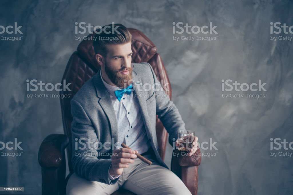 Portrait of handsome elegant young red bearded man holding glass of...