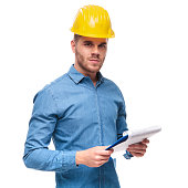 portrait of handsome engineer with clipboard in hand and safety helmet on head, standing on white background