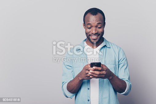 istock Portrait of handsome excited cheerful joyful delightful curious guy wearing casual jeans denim shirt sending and getting messages to his lover isolated on gray background 925451818