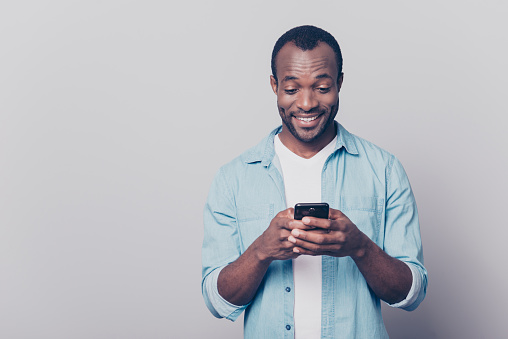Portrait of handsome excited cheerful joyful delightful curious guy wearing casual jeans denim shirt sending and getting messages to his lover isolated on gray background