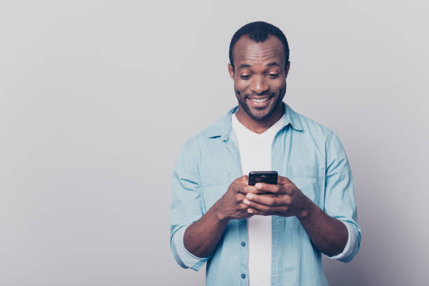portrait of handsome excited cheerful joyful delightful curious guy wearing casual jeans denim shirt sending and getting messages to his lover isolated on gray background - text messaging stock photos and pictures