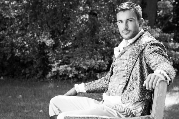 porträt von stattlichen gentleman in vintage-kostüm sitzen auf der bank im garten gekleidet - bräutigam anzug vintage stock-fotos und bilder