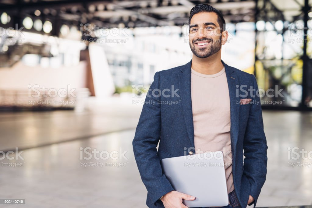 Portrait of handsome Indian guy with laptop stock photo