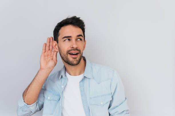 portrait of handsome interested male placing hand on ear asking someone to speak up, isolated over white background. young stylish man which overhears conversation in the studio. copy space for text. - ear stock photos and pictures