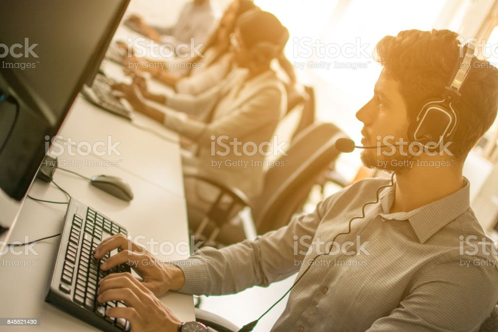 Portrait of handsome male customer service representative, call centre worker, agent, operator, support staff speaking with head set in modern office. stock photo