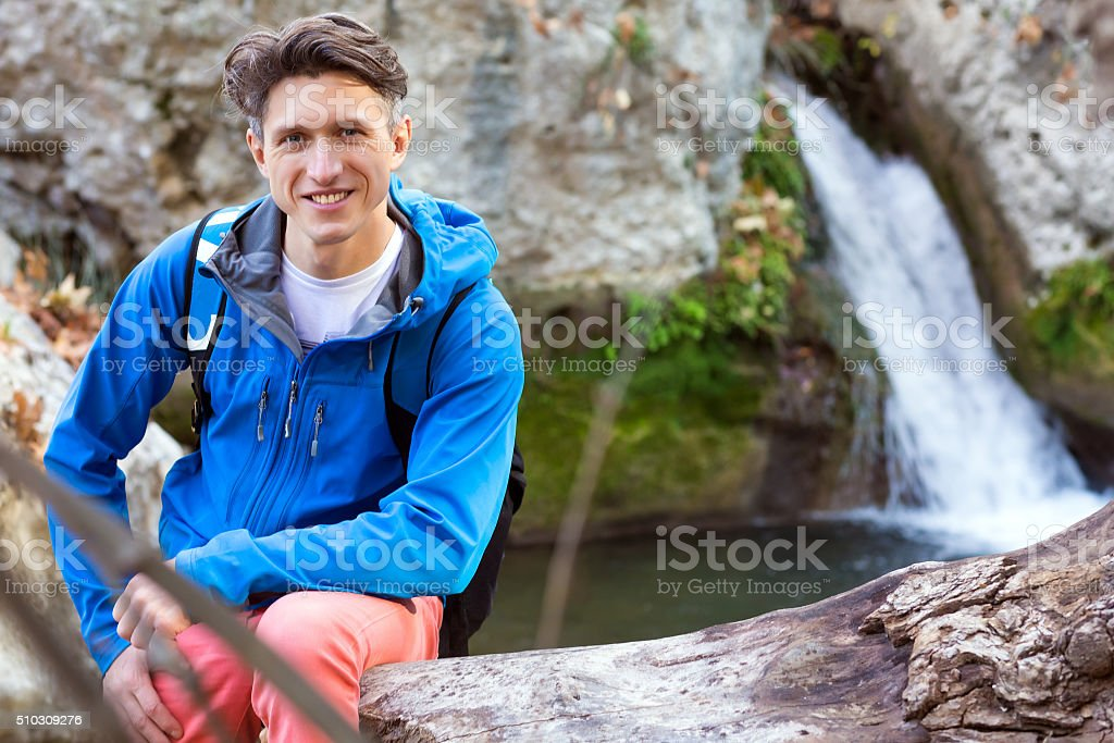 Portrait of handsome male Hiker sitting tree trench at lake stock photo