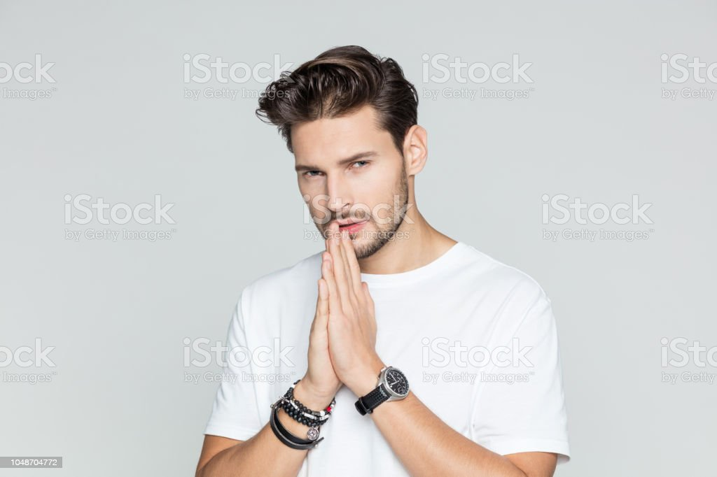 Portrait of handsome male model Portrait of handsome male model looking at camera on grey background 25-29 Years Stock Photo