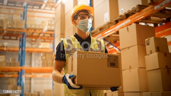 Portrait of Handsome Male Worker Wearing Medical Face Mask and Hard Hat Carries Cardboard Box Walks Through Retail Warehouse full of Shelves with Goods. Safety First Protective Workplace.