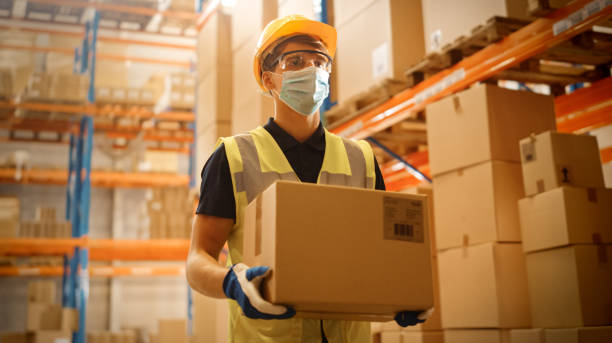 Portrait of Handsome Male Worker Wearing Medical Face Mask and Hard Hat Carries Cardboard Box Walks Through Retail Warehouse full of Shelves with Goods. Safety First Protective Workplace. stock photo