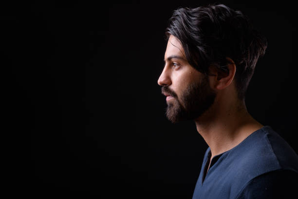 portrait of handsome man against black background - profile view stock photos and pictures