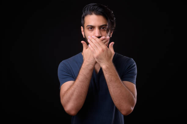 Portrait Of Handsome Man Covering His Mouth Against Black Background stock photo