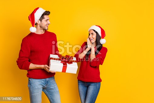 istock Portrait of handsome man give package for his impressed sweetheart screaming wow omg wear red cap pullover denim jeans isolated over yellow background 1176734520