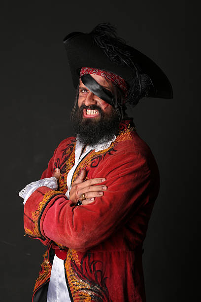 Portrait of handsome man in a pirate costume Portrait of handsome man in a pirate costume with hat and eye patch on black background pirate criminal stock pictures, royalty-free photos & images