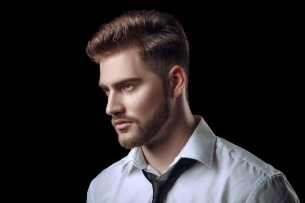 porträt von gut aussehender mann in einem studio auf einem dunklen hintergrund - männerfrisuren stock-fotos und bilder