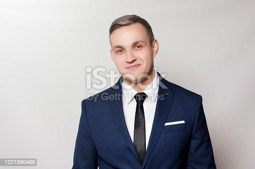 906807208 istock photo Portrait of handsome man in black blue suit 1221590465