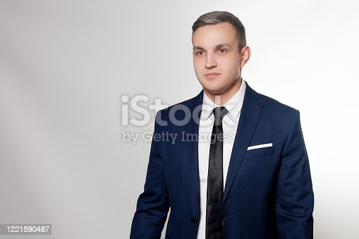 906807208 istock photo Portrait of handsome man in black blue suit 1221590487