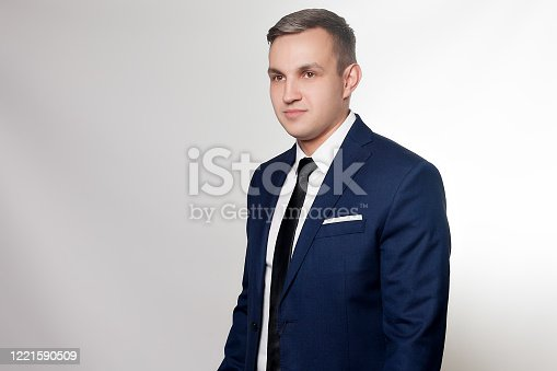 906807208 istock photo Portrait of handsome man in black blue suit 1221590509