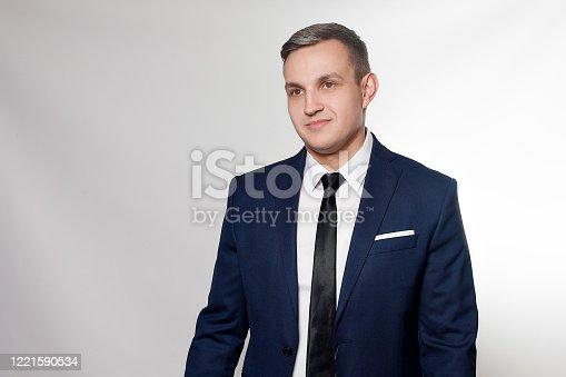 906807208 istock photo Portrait of handsome man in black blue suit 1221590534