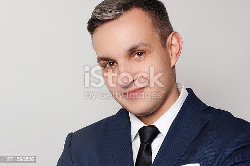 906807208 istock photo Portrait of handsome man in black blue suit 1221590536