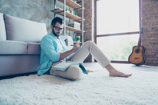 Portrait of handsome man in glasses having book and copybook on his legs, sitting near sofa on the floor, doing writing exercise stock photo
