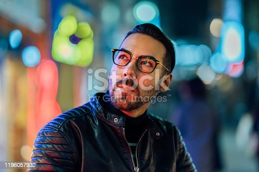 A close up portrait of a handsome man lit by neon lights at night.