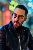istock Portrait of handsome man lit by neon lights at night 1196057973