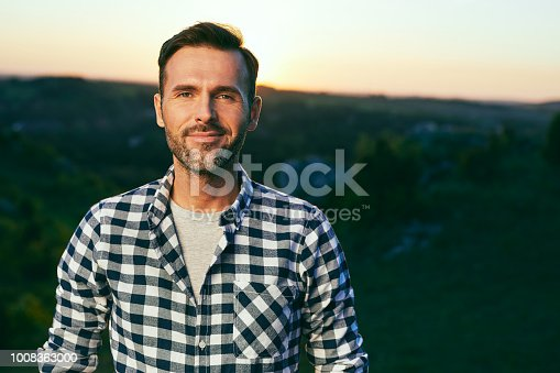 istock Portrait of handsome man standing on meadow surrounded by nature 1008363000