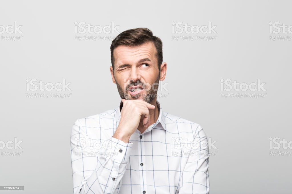 Portrait of handsome man thinking with hand on chin stock photo