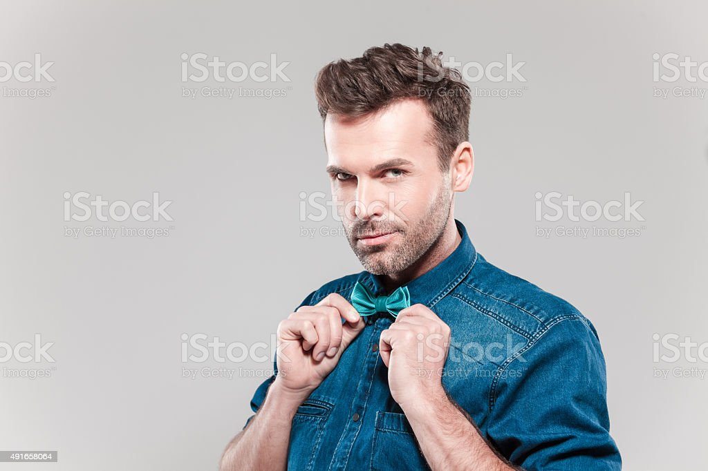 Portrait of handsome man wearing jeans shirt and bow tie Portrait of handsome man wearing jeans shirt and bow tie, smirking, looking at camera. Studio shot, grey background. 2015 Stock Photo