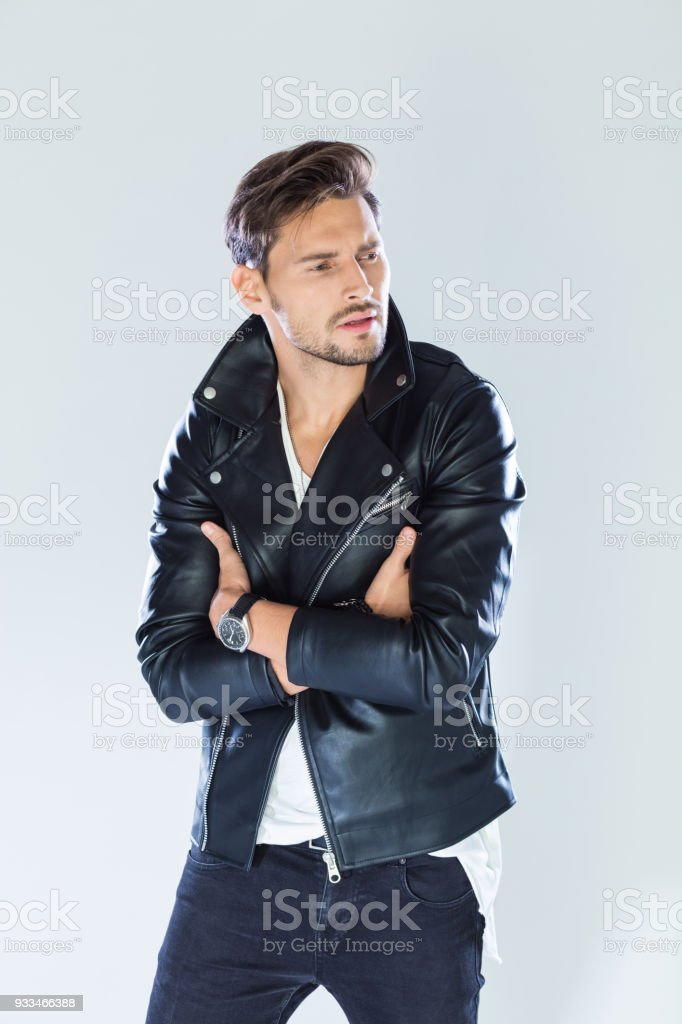 Portrait of handsome man wearing leather jacket Fashion portrait of handsome man wearing black leather jacket. Studio shot, grey background. 25-29 Years Stock Photo
