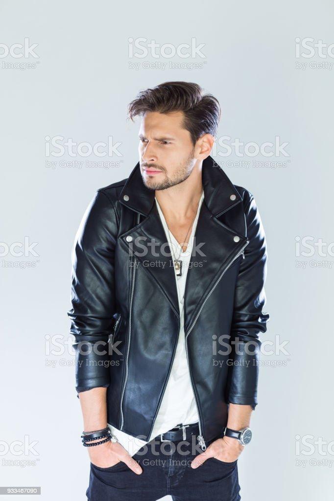 Portrait of handsome man wearing leather jacket Fashion portrait of handsome man wearing black leather jacket. Studio shot, grey background. 25-29 Years Stock Photo