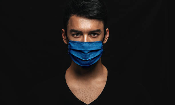 Portrait of handsome man wearing medical blue mask on the face during virus epidemic lockdown posing on black wall. Caucasian male with disposable face mask to prevent the virus. Coronavirus, health stock photo