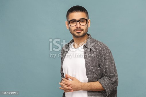 Portrait of bearded handsome man with black glasses in casual style looking at camera and smiling. studio shot on blue background.