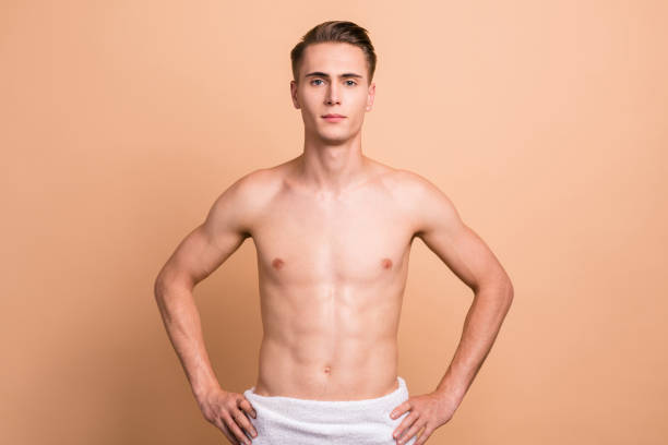 portrait of handsome man with towel, naked torso, looking relax after bath, going to take shower, standing isolated on pastel beige background - a petto nudo foto e immagini stock