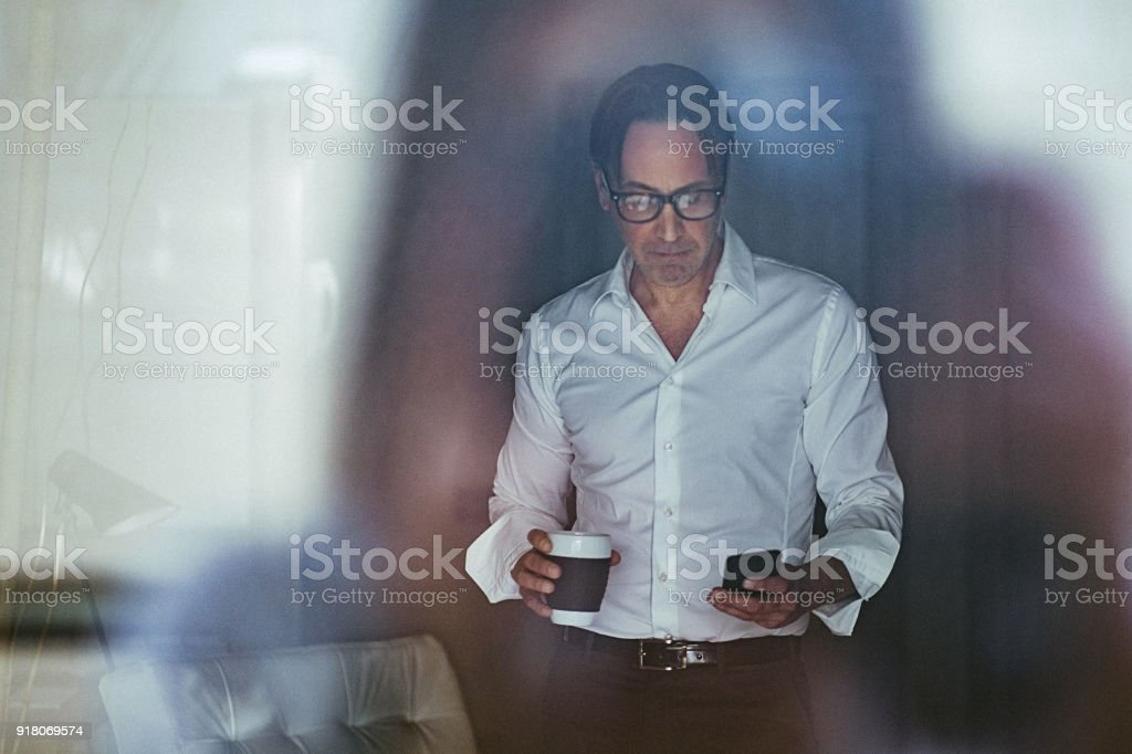 Portrait of handsome mature businessman having coffee and using mobile phone inside modern office space stock photo