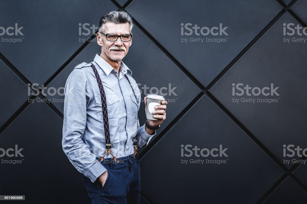 Mature businessman holding cup of coffee and looking at camera while...